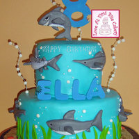 Sharks Fondant covered cake with hand-molded fondant sharks attached to the sides with royal icing. Base has fondant green plants and orange...
