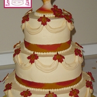 Autumn Leaves Wedding Buttercream tiered wedding cake with cream-colored fondant swags. Fondant leaves and fondant ribbons were made and hand-painted to match...