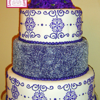 Royal Purple Wedding Three tiers are covered in fondant. The top and bottom tiers have the center pattern stenciled onto the fondant with thinned purple royal...