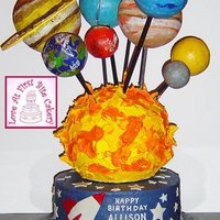 Outer Space Solar System Base cake is buttercream covered with fondant star/spaceship cutouts. Bottom boarder is silver florist wire wrapped around a dowel to give...