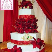 Poinsettia Red & Gold Wedding Cake The hexagon, buttercream wedding cake is trimmed in silk poinsettia and golden twigs. A patterned, store-bought ribbon encircles the base...