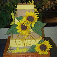 More Bridal Show Display Cakes Summer themed display cake. Yellow fondant with silk flowers and burlap borders. Custom built plateau.