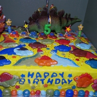 "Dinosaur Celebration This is my dino crazy grandson's 5th bday cake. Crusting buttercream frosting. All fondant decorations. Used ""Pluffy"" molds..."