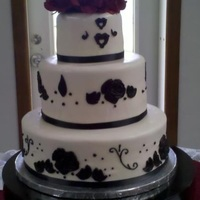 Wedding Cake Three tier - covered in marshmallow fondant with black pieces from molds and free-hand cutout. Topped with red roses. All bride designed to...