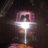 Theater   Edible image of the couple with fondant background and curtains on an orange buttercream cake. Cupcakes in orange, purple & pink.