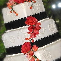 Square Wedding Cake Orange freesias and roses, and black fondant ribbon border.