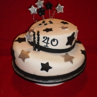 "Mariline  12"" cake covered with fondant. Stars of the cake were fondant, the rest were gumpaste and covered with black and silver edible glitter..."