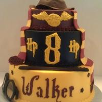 Harry Potter Birthday Cake Harry Potter cake in buttercream with fondant trim, fondant scarf, wand, and hat. glasses are made of fondant and dugar glass candy.