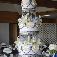 Sapphire And Ivory Cake Elegant wedding cake with Sapphire blue pearls, gems, roses. All tiers are separated by silver chandelier stands.