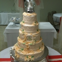 Peaches And Cream 5 tiers, all yellow with buttercream. Airbrushed with pearl sheen. Flowers are all modeling chocolate