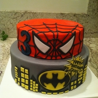 Superhero 8 inch and 10 inch round cakes covered in fondant with fondant accents. TFL