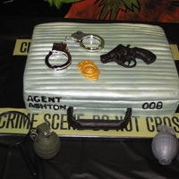 Spy Birthday Party Cake Cake is iced in buttercream and then air brushed. The gun and badge are made from fondant.