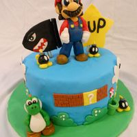 Super Mario Bros Birthday Cake This cake is all edible. Hand Molded Mario and Yoshi along with various Super Mario Bros Characters. Chocolate Cake with Oreo Buttercream...