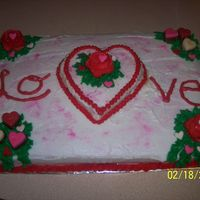 Love Cake  9x13 white cake with a small heart made out of white cake in center. Iced in buttercream with buttercream roses, heart sprinkles, pink...
