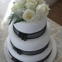 Cream Roses Cake   3 tiers of chocolate cake with fondant icing, black ribbon and fresh cream roses