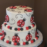 2 Tier Lady Bug Cake This is a 6 and 8 inch cake covered in buttercream with lady bug accents. I cut the lady bugs out with round pieces of fondant.