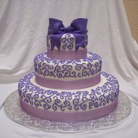 Shades Of Purple  This was a wedding cake for a bride who wanted several different shades of purple. Fondant with royal icing scroll work and fondant bow....