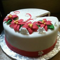 Poinsetta Christmas Cake Red Velvet cake, flowers are gumpaste, sugar pressed snowflakes, and fondant covered.