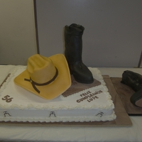 Cowboy Birthday hat and both boots are cake sitting on a full sheet cake.