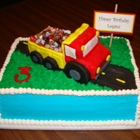 Dump Truck Buttercream covered cake with grass tip for lawn. Road is fondant with fondant dashes. The dump truck is rice crispy treats covered with...