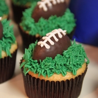 Football Cupcakes Cupcakes frosted with Buttercream, topped with a chocolate coated cake ball. Made these for a Superbowl party! Giants vs. Patriots