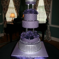 Purple Wedding Cake purple fondant with silver fondant and silver dragees. sugar flowers-anenomes and calla lillies.