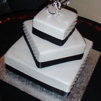 Valentine's Day Wedding Cake 3 tiers of Red Velvet cake, w/ cream cheese filling, covered in white fondant, and decorated w/ a black satin ribbon, and white pearls.The...