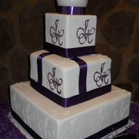 Purple And White Wedding Cake Chocolate cake with Amarula Ganache filling. The topper is a candle and the initials was embossed with RI