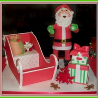 Santa Clause Is Coming Too Town  all edible cake is sleigh seat gift boxes and santa's tummy. there is a pvc inner support structure for Santa his legs and arms are...
