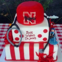 Retirement Retirement cake depicts interests - fisherman on one side, bird hunter w/faithful dog on the other, stethoscope and Nebraska Huskers...