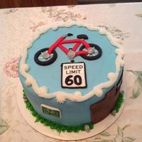"Cycling To 60   *8"" round buttercream with fondant decorations."