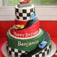 Racecar Birthday Buttercream with fondant accents and real, die cast cars.