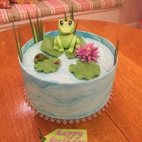 "Frog Birthday Cake White vanilla bean cake with strawberry filling and iced with butter cream. Cake is ""wrapped"" in white chocolate clay colored to..."