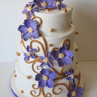Purple And Gold Wedding Stacked round tieres with purple gumpaste flowers and gold swirls and beads.