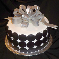 Circles Cake covered in white fondant, black fondant circles and silver fondant bow. TFL!