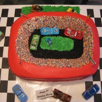 Race Track Yellow cake. Buttercream frosting. Rainbow Nonpareils as the people in the stands and black sugar as the track. The mother supplied the...