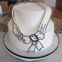 "Drawn Bow Cake 9"" and 6"" tiers. Cake is chocolate with raspberry filling. Buttercream iding and fondant ribbon and bow."