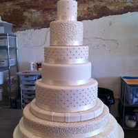 1315278634.jpg its a 7 tier wedding cake covered in an ivery fondant. Ribbon and rhinestones are placed at the base of each tier