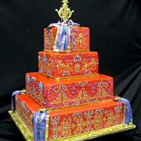 Colorful Indian Wedding Cake  Cake is covered in red fondant. Gold design is stenciled on the cake. The rest of the design is piped in icing.Drapes on the corners and on...