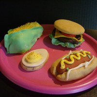 Summer Treats The corn is a mini cake. The hot dog is a sugar cookie. The hamburger is also a sugar cookie with a chocolate dipped burger. The egg is...