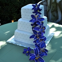 Lily Wedding Cake September wedding. Three different flavors. Gumpaste lilies, hand painted. Fondant quilted pattern.