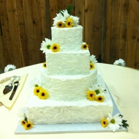 Bride's Rustic Butter Cream Iced Cake WASC 16 square, 12 round, 8 square and 6 inch round iced with butter cream rustic look and trimmed with real sunflowers and daisies.