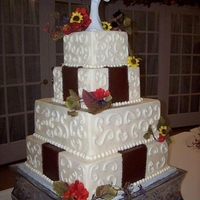 Square Wedding Cake WASC iced with butter cream. Wide brown butter cream ribbon trim down the center of bottom and 2nd tier with scrolls on every tier. Silk...