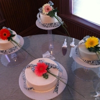 Round Wedding Cakes WASC round cakes on individual cake stands trimmed with pearl borders, live daisies and zebra print floral ribbon. Iced with Butter cream...