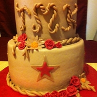 Country Style Wedding Shower Cake Two tier 10 and 6 inch yellow butter flavored cake iced with chocolate butter cream. Country red and tan stars, roses and diasies. Fondant...