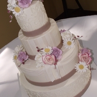Buttercream Wedding Cake With Swags Four tier buttercream cake with brush embroidery, fondant swags, ribbons and scroll work. Sugarf flowers