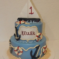 Nautical First Birthday Cake two tier fondant birthday cake with sailboat cake topper, anchors and life perservers.