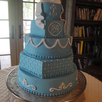 Liz's Blue Cake 5-tier round and hexagon cake with blue buttercream and white piping.