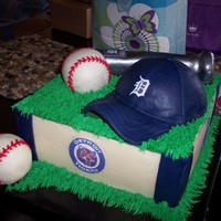 Detroit Tigers Grooms Cake banana cake with banana cream filling. covered in modeling chocolate. Hat is chocolate, baseballs are cake covered in chocolate and bat is...