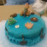 Fishing gum paste fisher on a gum paste deck with a gum paste frog and gum paste flowersblue fondant and cat tails and leaves. border was butter...